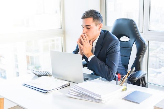 Ongerust gemaakte jonge zakenman die laptop in het bureau bekijkt Gratis Foto