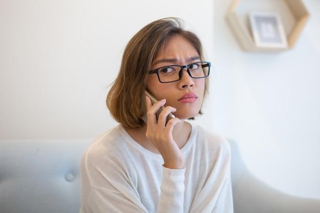 Ongerust gemaakte vrouw die smartphone op bank thuis uitnodigen Gratis Foto