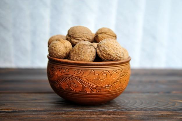 Ongeschilde walnoten in aardewerk op een houten tafel Premium Foto