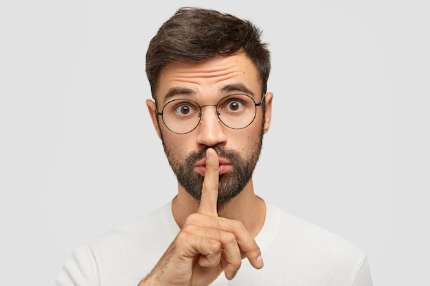 Ongeschoren blanke man maakt stilte gebaar, vraagt om stil te zijn als iemand slaapt, bril draagt, trendy kapsel heeft, geïsoleerd over een witte muur. mensen, samenzwering en geheimhouding concept Gratis Foto