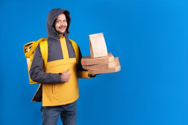 Ongeschoren donkerharige blanke koerier in geel windjack houdt een bestelling van pizza Premium Foto