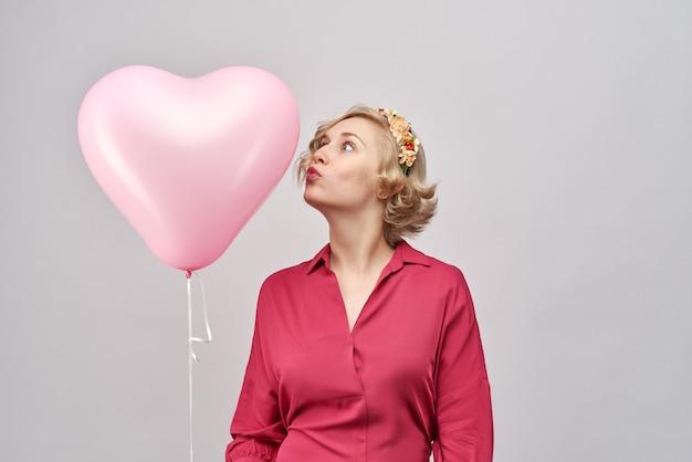 Ongewoon aantrekkelijk jong meisje in een rode jurk en met een krans op haar hoofd houdt een ballon in de vorm van harten en kust hem. het concept van liefde, valentijnsdag, verras je geliefde Premium Foto