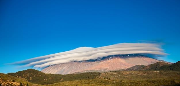 Ongewoon uitzicht op de berg teide bedekt met de hoed van wolken, tenerife, spanje Premium Foto