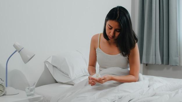 Ongezond ziek indiaas vrouwtje lijdt aan slapeloosheid. aziatische jonge vrouw die pijnstillergeneeskunde neemt om hoofdpijnpijn te verlichten en glas waterzitting op bed in haar slaapkamer thuis in ochtend te drinken. Gratis Foto
