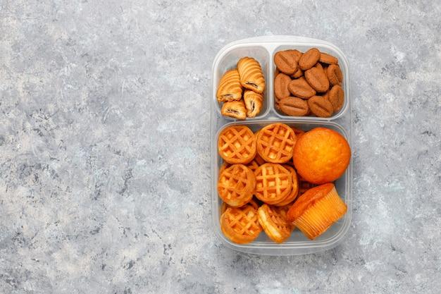 Ongezonde lunchdoos met koekjes, wafels. muffins op concrete oppervlakte Gratis Foto