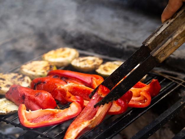 Onherkenbaar kok flipping plakjes paprika op barbecue rooster Gratis Foto