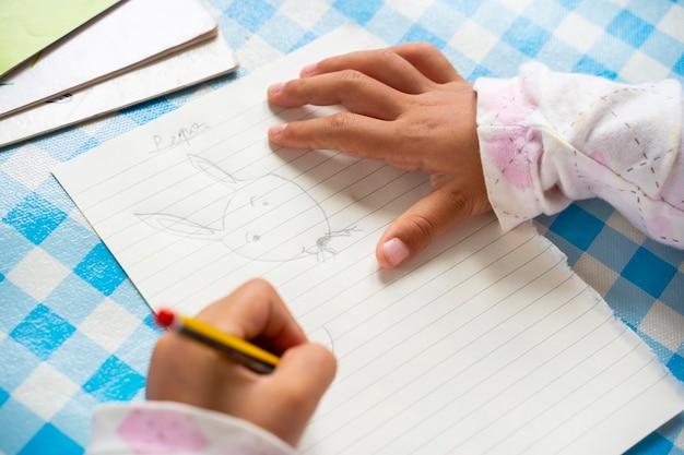 Onherkenbaar linkshandig kind dat een tekenfilm konijn tekent op een vel papier. meisje dat een potlood houdt en creativiteit onderzoekt. vrije tijd voor kinderen concept. levensstijl met kinderen thuis. Premium Foto