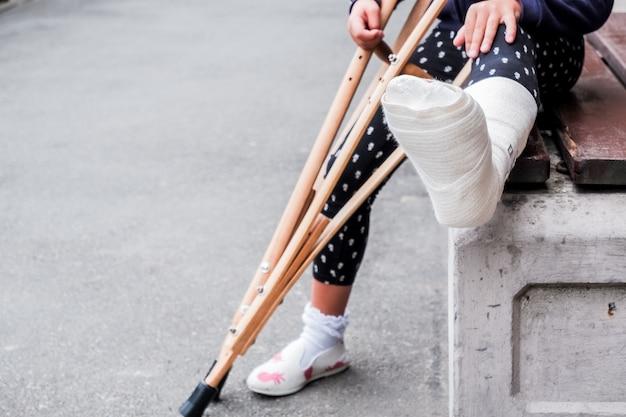 Onherkenbaar meisje zit op straat op een bank met een gebroken been en krukken. Premium Foto