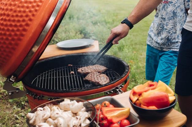 Onherkenbaar mensen kokend vlees bij de grill. Premium Foto