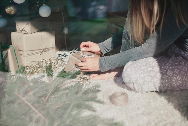Onherkenbaar persoon die geschenken voor haar gezin voorbereidt Gratis Foto