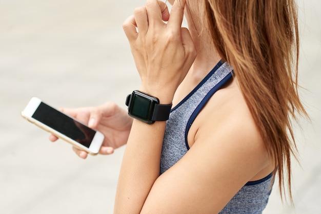 Onherkenbare atletische vrouw met slim horloge die impuls controleren en smartphone gebruiken Gratis Foto