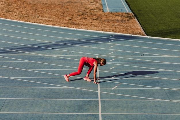 Onherkenbare fitness vrouw op stadion uitgevoerd door blauwe tracks Premium Foto