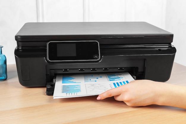 Onherkenbare jonge onderneemster die kopieën maken op de fotokopiemachine op kantoor Premium Foto