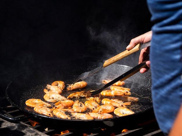 Onherkenbare kok flipping garnalen frituren op grote pan Gratis Foto