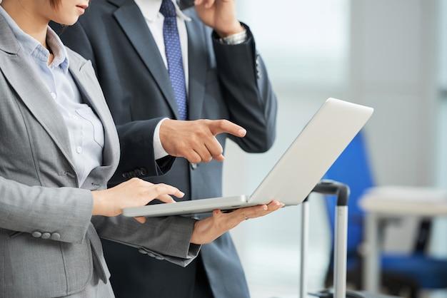 Onherkenbare man en vrouw in pak kijken laptop scherm samen Gratis Foto