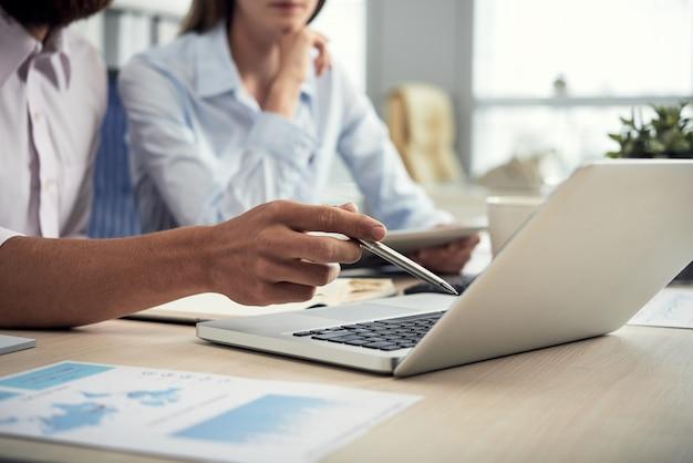 Onherkenbare mannelijke en vrouwelijke collega's die laptop het scherm in bureau bekijken Gratis Foto