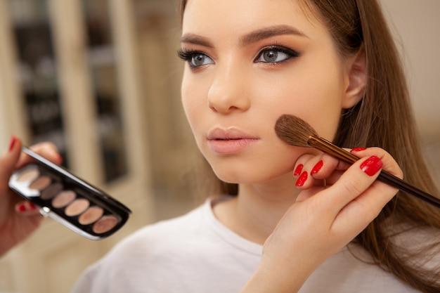 Onherkenbare visagist die een markeerstift op de huid van een vrouwelijke klant aanbrengt Premium Foto