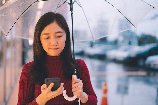 Onherkenbare vrouw die lang over straat loopt terwijl het regent, natte betonweg van regenstorm Premium Foto