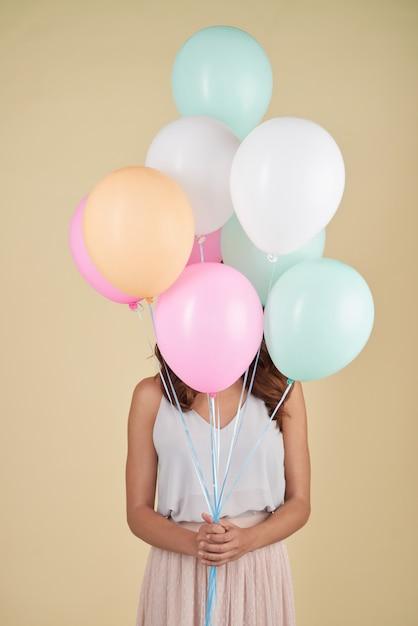 Onherkenbare vrouw poseren in studio met haar gezicht bedekt met ballonnen Gratis Foto