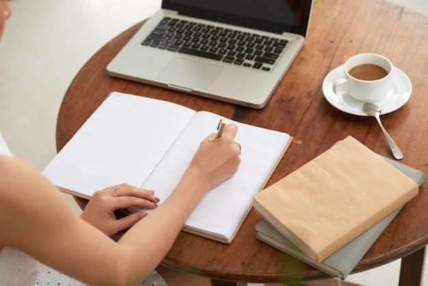 Onherkenbare vrouwenzitting in koffie met laptop en het schrijven in dagboek Gratis Foto