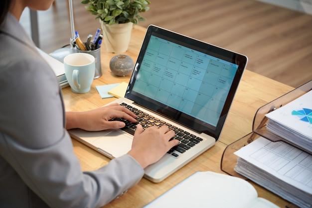 Onherkenbare zakenvrouw zit aan bureau met laptop en kijken naar kalender Gratis Foto