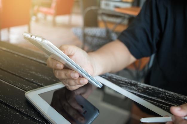Online bankieren betalen via netwerktechnologie internet op draadloze ontwikkeling mobiel synchroniseren van smartphone en tablet met aanraakpen voor zakelijk gebruik van smart phone voor winkelen coffeeshop Premium Foto