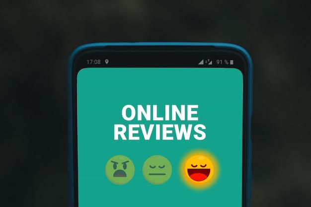 Online beoordelingen services of organisatie. mobiele telefoon scherm met emoticons glimlacht Premium Foto