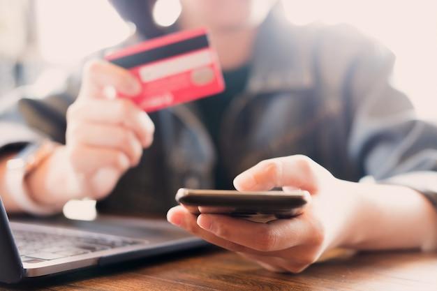 Online betaling, young man's handen met behulp van computer en hand met creditcard voor online winkelen. Premium Foto