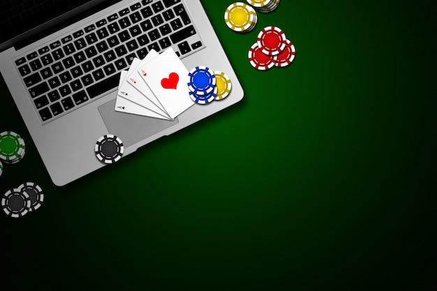 Online casino, laptop, chipskaarten op groen Premium Foto