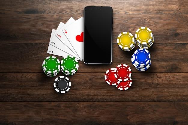 Online casino, mobiel casino, bovenaanzicht van een mobiele telefoon, chipskaarten op hout Premium Foto