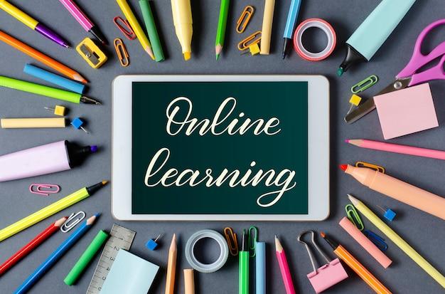 Online leren - handgeschreven inscriptie op een tablet. het concept van afstandstraining voor kinderen. tablet en kantoorbenodigdheden op een donkere achtergrond. Premium Foto