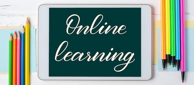 Online leren - handgeschreven inscriptie op een tablet. het concept van afstandstraining voor kinderen. tablet en kantoorbenodigdheden op een witte houten achtergrond. Premium Foto
