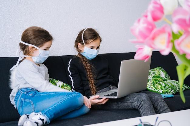 Online onderwijs, afstandsonderwijs, thuisonderwijs. kinderen die thuiswerk tijdens online les thuis in tablet van laptop bestuderen en videocall houden. sociale afstand in quarantaine. zelfisolatie Premium Foto