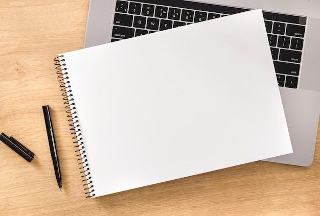 Online onderwijsconcept leeg notitieboekje met laptop en pen op houten lijstbovenaanzicht Premium Foto
