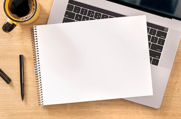 Online werk of onderwijs concept leeg notitieboekje met laptop en kopkoffie op houten lijstbovenaanzicht Premium Foto