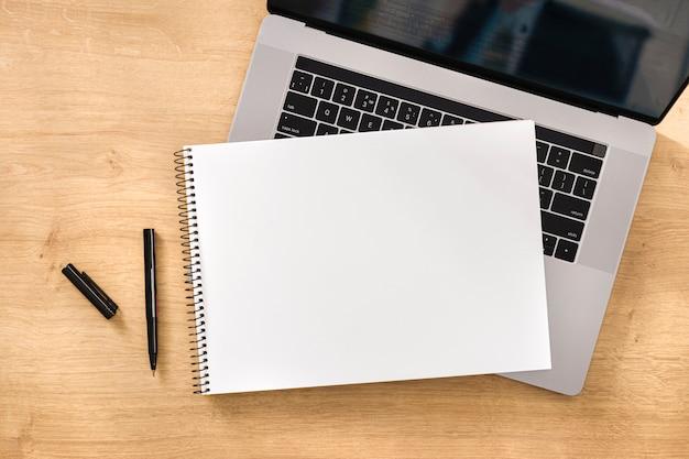 Online werk of onderwijs concept leeg notitieboekje met laptop op houten tafelblad bekijken Premium Foto