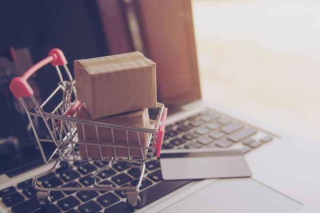 Online winkelconcept - winkelen op het online-web. kartons met een winkelpin Premium Foto
