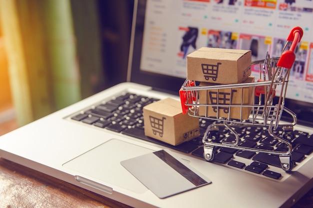 Online winkelen concept - pakket of papier dozen met een winkelwagentje logo in een trolley op een laptop toetsenbord. Premium Foto