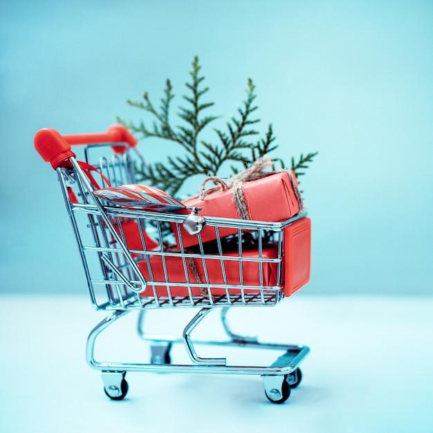 Online winkelen concept - trolley vol geschenken. black friday en cyber monday Premium Foto