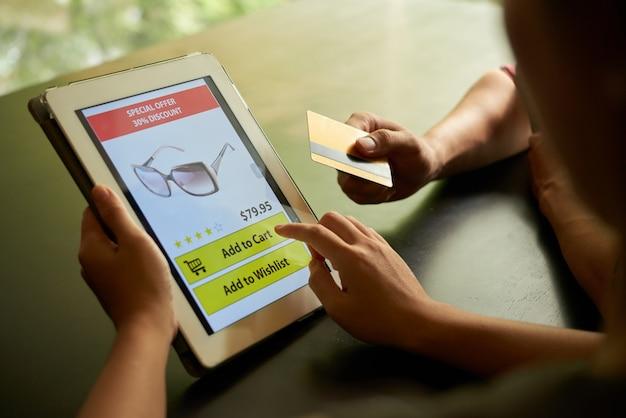 Online winkelen concept van twee onherkenbare mensen die een zonnebril toevoegen aan winkelwagen op de tablet-pc Gratis Foto