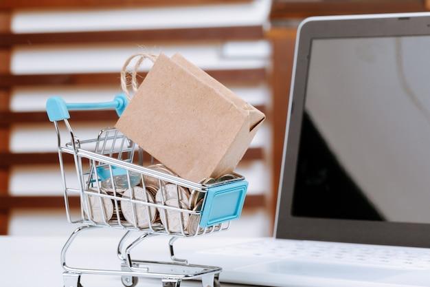 Online winkelen concept. winkelwagen, laptop op het bureau Premium Foto