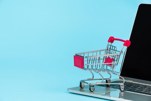 Online winkelen, een winkelwagentje naast een notitieblok op een blauwe. Gratis Foto
