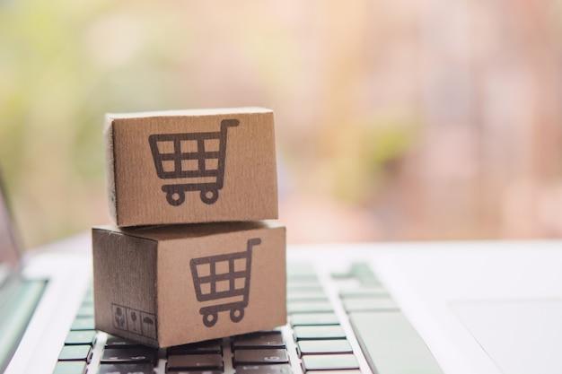 Online winkelen - papieren dozen of pakjes met een winkelwagentje-logo op een laptoptoetsenbord. boodschappenservice op het online web en biedt levering aan huis. Premium Foto