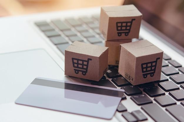 Online winkelen - papieren dozen of pakket met een winkelwagenlogo en creditcard op laptop toetsenbord. boodschappenservice op het online web en biedt bezorging aan huis. Premium Foto