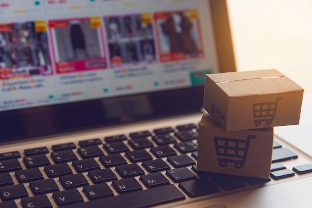 Online winkelen: papieren dozen of pakket met een winkelwagentje-logo op een laptoptoetsenbord. shopping-service op het online-web en biedt levering aan huis. Premium Foto
