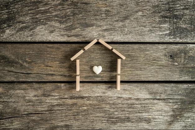 Onroerend goed concept met een hart in het frame van een huis op een tafel in hoge hoekmening. Premium Foto