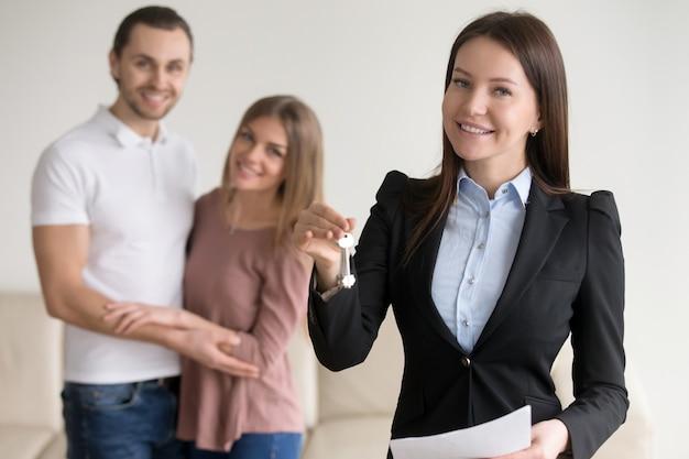 Onroerend goed deal. vrouwelijke glimlachende makelaar in onroerend goed die sleutels tonen aan vlakte Gratis Foto