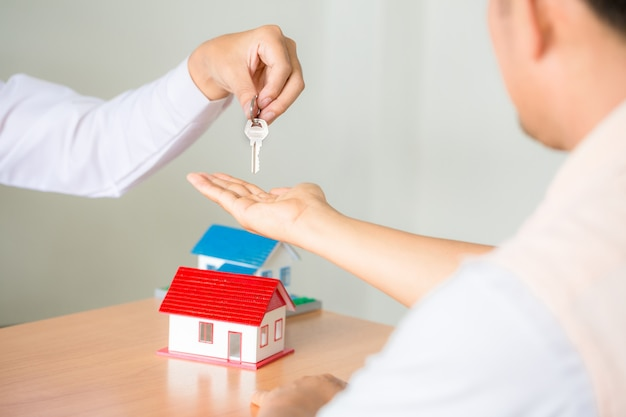 Onroerend goed verkoopmanager die sleutels geeft aan klant na ondertekening huurleasecontract of verkoopaankoopovereenkomst Gratis Foto