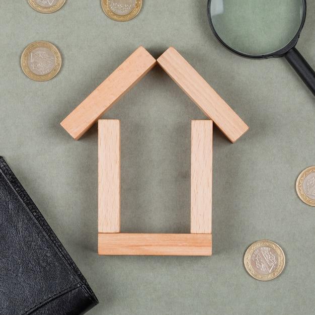 Onroerende goederen en financieel concept met houten blokken, vergrootglas, notitieboekje, muntstukken op grijs close-up als achtergrond. Gratis Foto