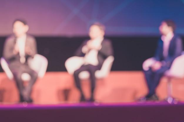 Onscherpe achtergrond van sprekers op het toneel in de conferentiezaal of seminarievergadering, bedrijfs en onderwijsconcept Premium Foto